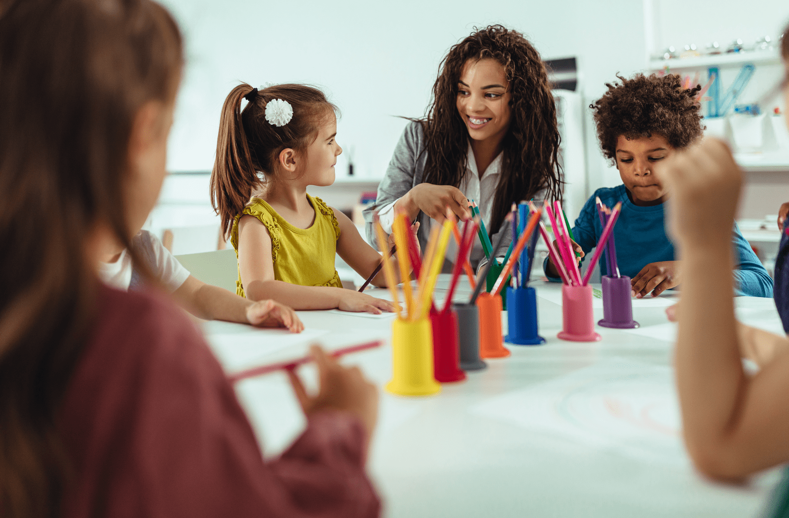 Teacher at a daycare painting with a group of happy children