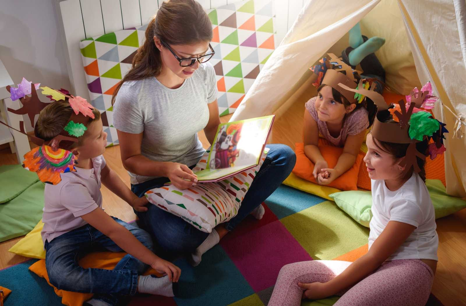 young woman reading to daycare children wearing paper crafts on their heads