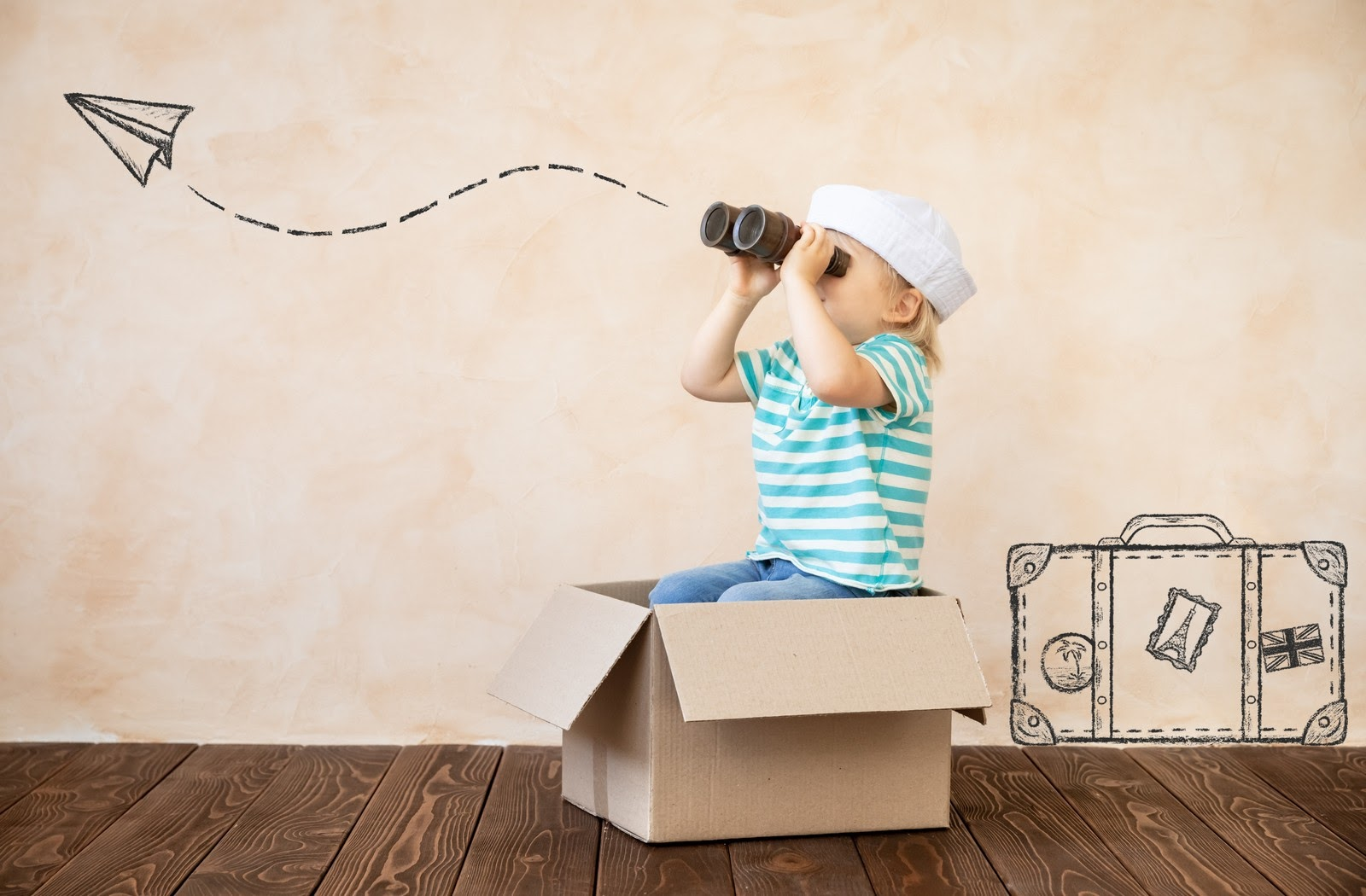young boy dressed as a sailor holding binoculars while sitting in a cardboard box imagining a paper plane flying away